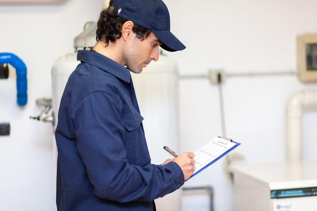 Technician servicing a hot water cylinder maintenance