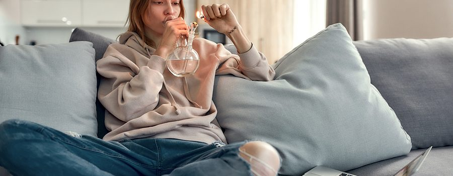 Young woman using glass water pipes for smoking